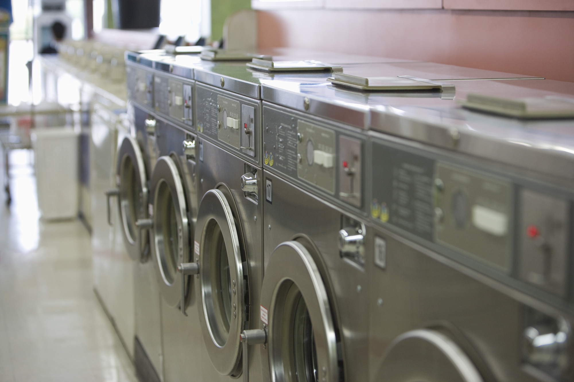 Row of commercial washing machines for laundry room leases at multifamily properties