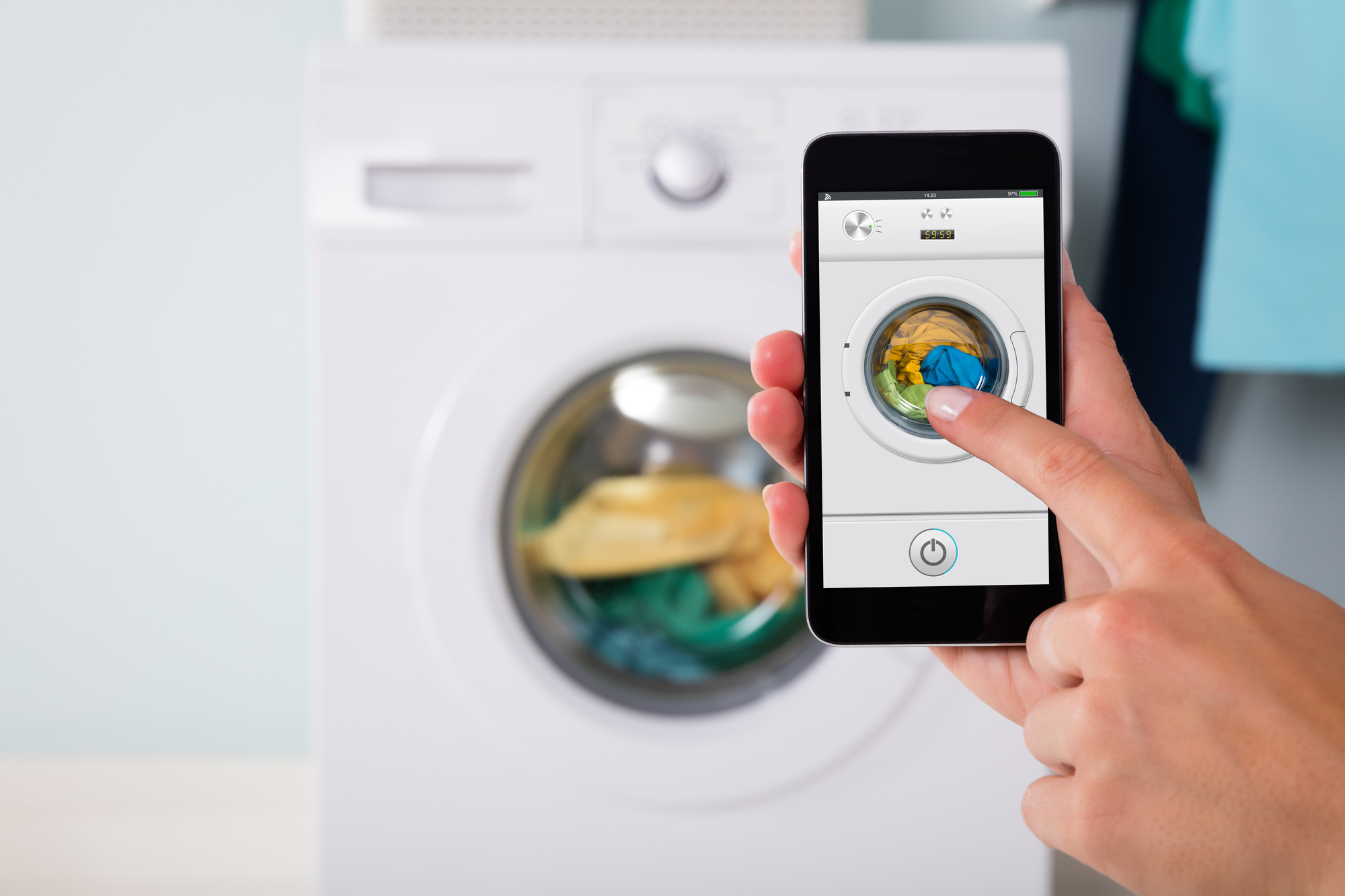 Person Using Laundry Room Mobile Apps On Smartphone To Control Washing Machine