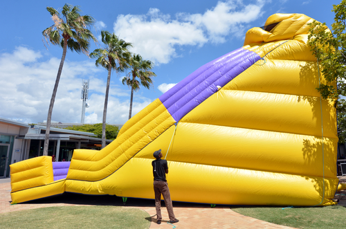 Worker Inflates Giant Bouncy Castle At Kids Related Apartment Resident Events
